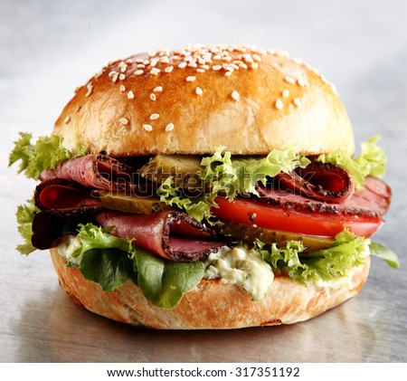 Roast beef or pastrami roll with salad trimmings and mayonnaise in a close up side view on a silver metallic counter at a takeaway restaurant - stock photo