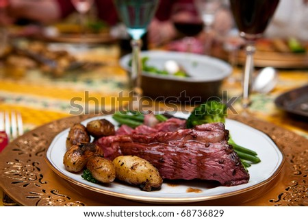 Roast beef with gravy and roasted potatoes side and green vegetables - stock photo