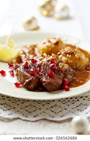 Roast beef  with onion-mushroom sauce and pomegranate seeds for Christmas - stock photo