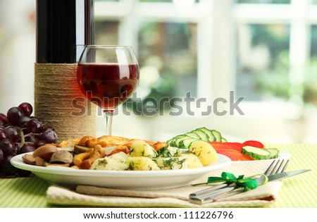 Roast chicken cutlet with boiled potatoes and cucumbers, glass of wine on green table cloth in cafe interior