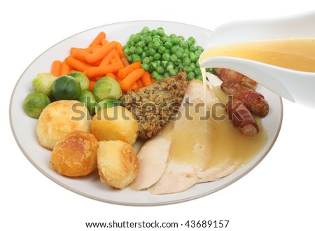 Roast chicken dinner with gravy being poured - stock photo