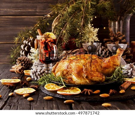 Roast chicken for Christmas and New Year with mulled wine and Christmas decorations, selective focus