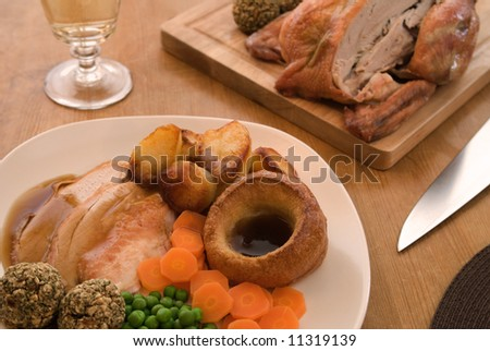 Roast chicken in a table setting - stock photo
