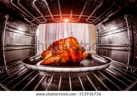 Roast chicken in the oven, view from the inside of the oven. Cooking in the oven. Thanksgiving Day. - stock photo