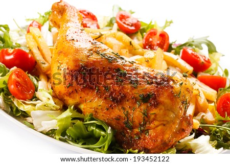 Roast chicken leg, French fries and vegetable salad - stock photo