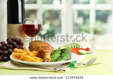 Roast chicken with french fries and cucumbers, glass of wine on green table cloth in cafe interior