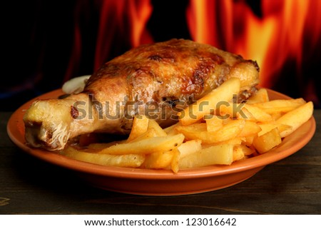 Roast chicken with french fries on fire background - stock photo