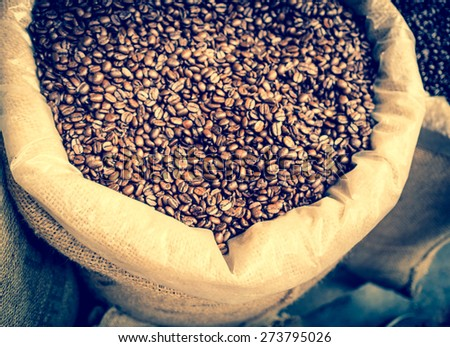 Roast coffee beans in retro style, top view. Big sack with roasted coffee, toned with instagram filter effect. Black coffee at vintage color with soft focus. - stock photo
