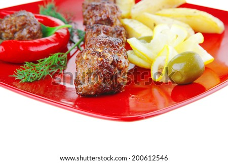 roast cutlets on red dish with peppers and potatoes - stock photo