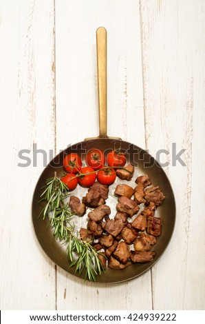 roast deer goulash with cherry tomatoes and rosemary in a brass pan - stock photo