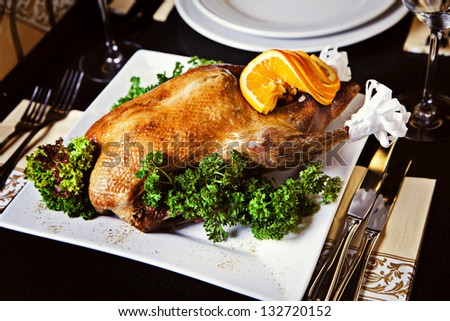 Roast duck served on a plate with parsley and orange - stock photo