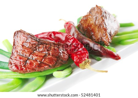 roast fillet mignon on a white ceramic plate with peppers