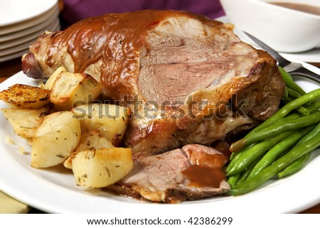 Roast leg of lamb, with string beans, roasted potatoes, and gravy.  Delicious! - stock photo
