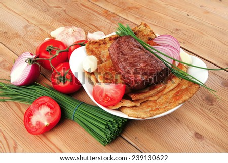 roast meat : beef ( lamb ) steak garnished with onion , tomatoes salad and chives, on wooden table - stock photo