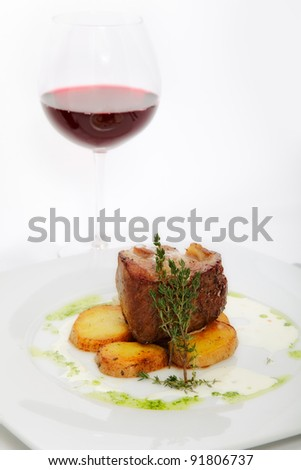roast meat with potatoes on white plate with glass of wine - stock photo