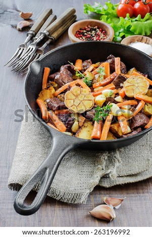 Roast meat with vegetables in a cast iron skillet on a wooden table