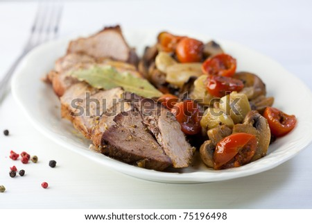 Roast pork with baked vegetables and mushrooms - stock photo
