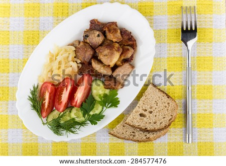 Roast pork with herbs and vegetables in platter, bread, fork and napkin on table, top view - stock photo
