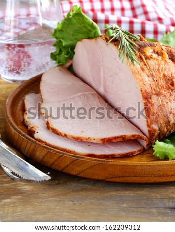 roast pork with paprika and rosemary served on a wooden plate - stock photo
