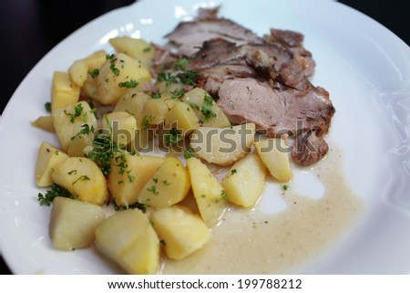 Roast pork with potatoes on a white plate - stock photo