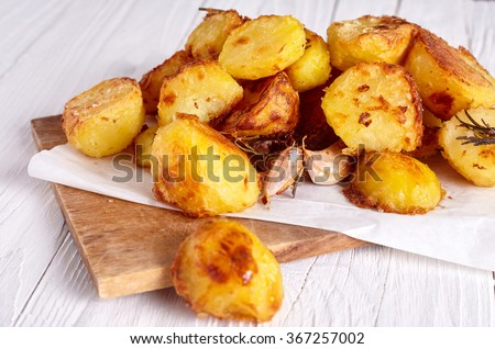 Roast potatoes seasoned with salt, garlic and provance herbs on wood background - stock photo