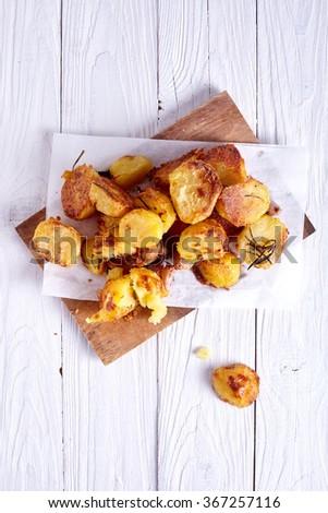 Roast potatoes seasoned with salt on wood background - stock photo
