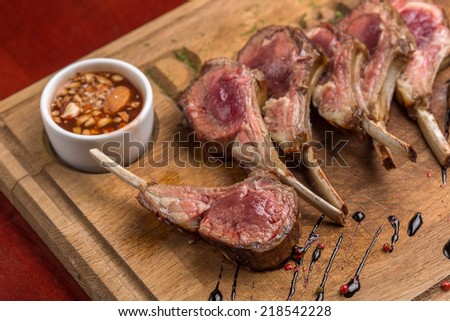 Roast rack of lamb served on wooden board