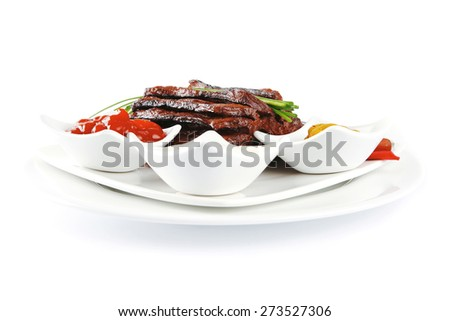 roast red beef meat fillet with red hot pepper with ketchup mayonnaise and mustard on plate isolated on white background - stock photo