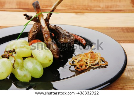roast ribs on wooden table with grapes - stock photo