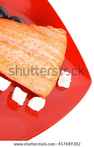 roast salmon fish meat fillet with lemon black greek olives white goat cheese on red plate isolated over white background - stock photo