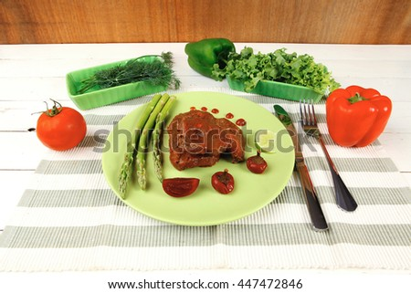 roast stew beef pork meat served with vegetables on green plate and cutlery on napkin over wooden table with red hot peppers - stock photo