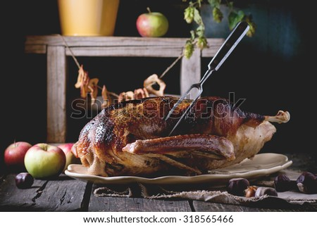 Roast stuffed goose with meat fork in on ceramic plate with ripe apples over wooden kitchen table. Dark rustic style. - stock photo