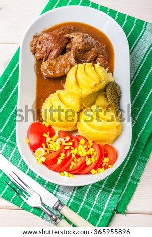 Roast turkey in gravy with potatoes, tomato and cucumber. - stock photo