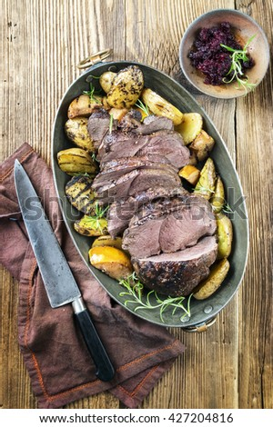 Roast Venison with Potatoes and Quince in Copper Pot - stock photo