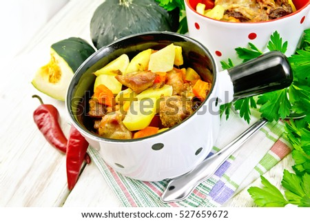 Roast with chicken, potatoes, squash and peppers in two portioned white pot on a towel, spoon, parsley on a wooden boards background