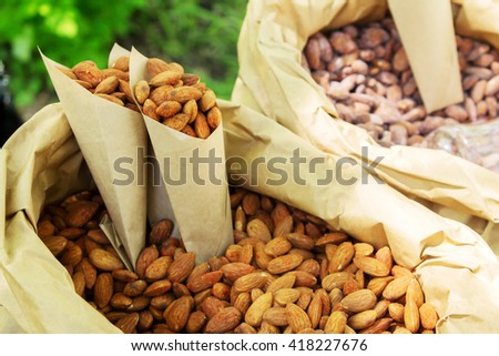 roasted almonds, pine nuts, hazelnuts, cashews and peanuts in sugar syrup with different tastes in paper envelope at festival of street food. Healthy peanuts diet. - stock photo