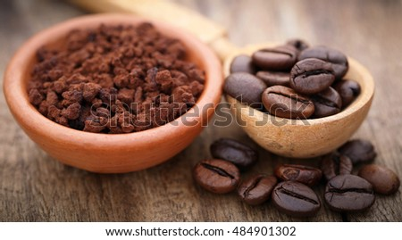 Roasted and crushed coffee bean in a wooden spoon and bowl
