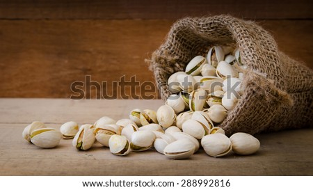 Roasted and Salted for Pistachios in a bag on wooden, Selective focus - stock photo
