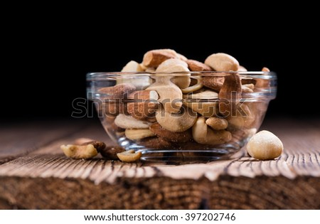 Roasted and salted nuts (mixed) on an old wooden table - stock photo