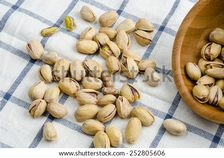 roasted and salted pistachios on table cloth - stock photo
