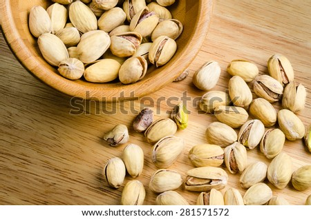 roasted and salted pistachios on wooden background - stock photo