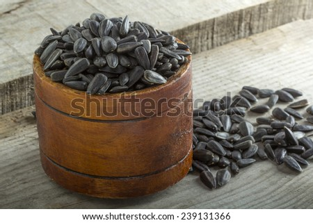 Roasted and salted sunflowers seeds in their shells, in bowl over old wood background - stock photo