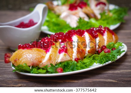 roasted baked chicken breast with cranberry and pomegranate sauce in a gravy boat on a wooden table - stock photo