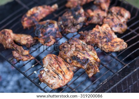 Roasted  barbecue meat on charcoals of grill.  Recipe or menu BBQ background