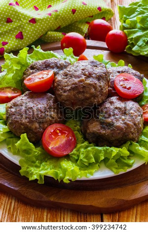 Roasted beef cutlets, green salad and small tomatoes on white plate. Wooden background. - stock photo