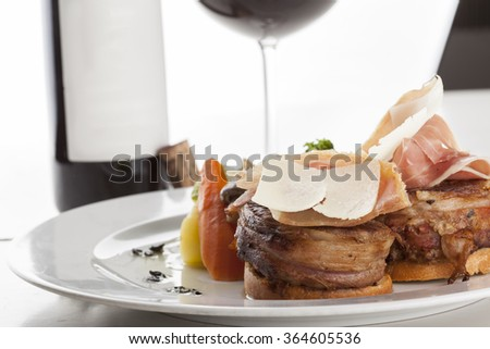 Roasted beef fillet on plate with wine glass and bottle