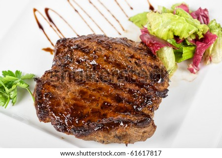 Roasted beef steak with vegetable closeup at plate