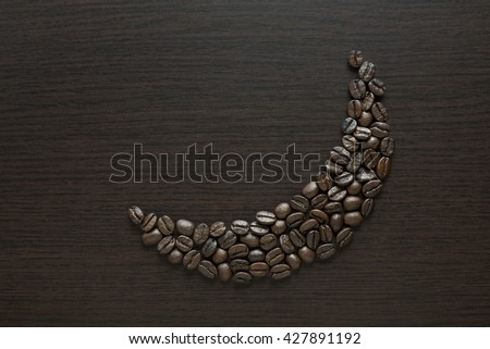 Roasted black coffee beans arranged in a moon shape on dark background. Coffee beans in moon shape - Ramadan food concept. - stock photo