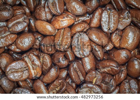 Roasted brown coffee beans texture background for design. Dark edged.