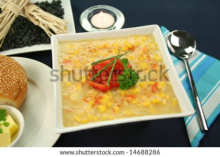 Roasted capsicum chili and corn chowder in a table setting. - stock photo